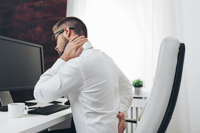 Office worker with neck pain from prolonged computer work on his work desk.