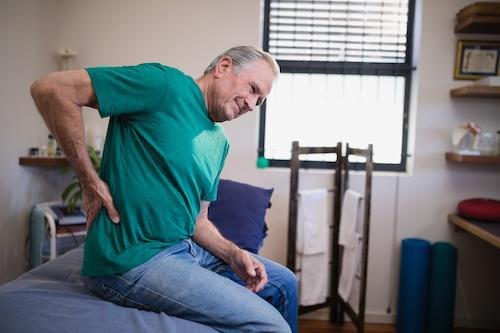 Elderly man sitting on his bed and experiencing back pain.