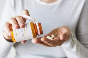 Lady pouring prescription drugs into her palm to relieve back pain