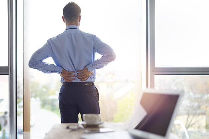 Back view of a business man holding his lower back because of back pain.