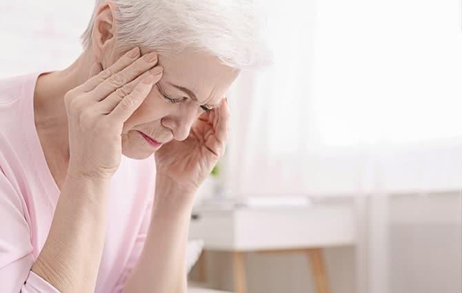 Senior woman touching her head due to headache.