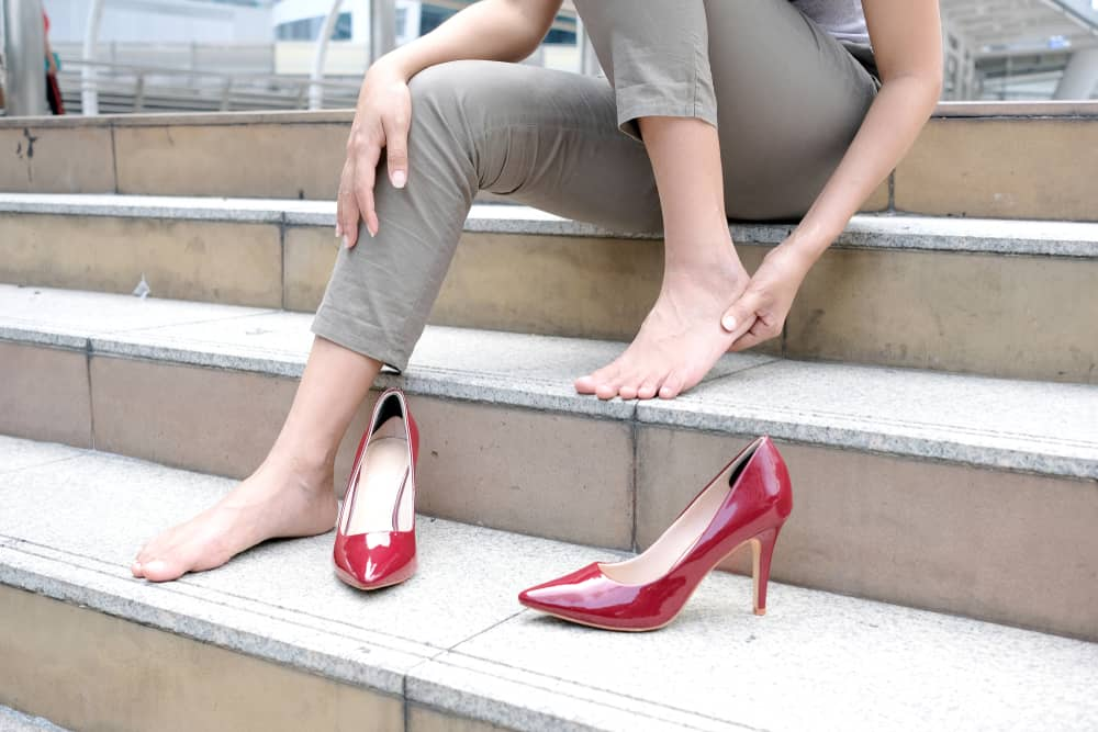 Woman removing her heels because of foot pain caused by neuropathy.