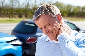 auto accident victim holding his painful neck with his car bumping into another car in the background