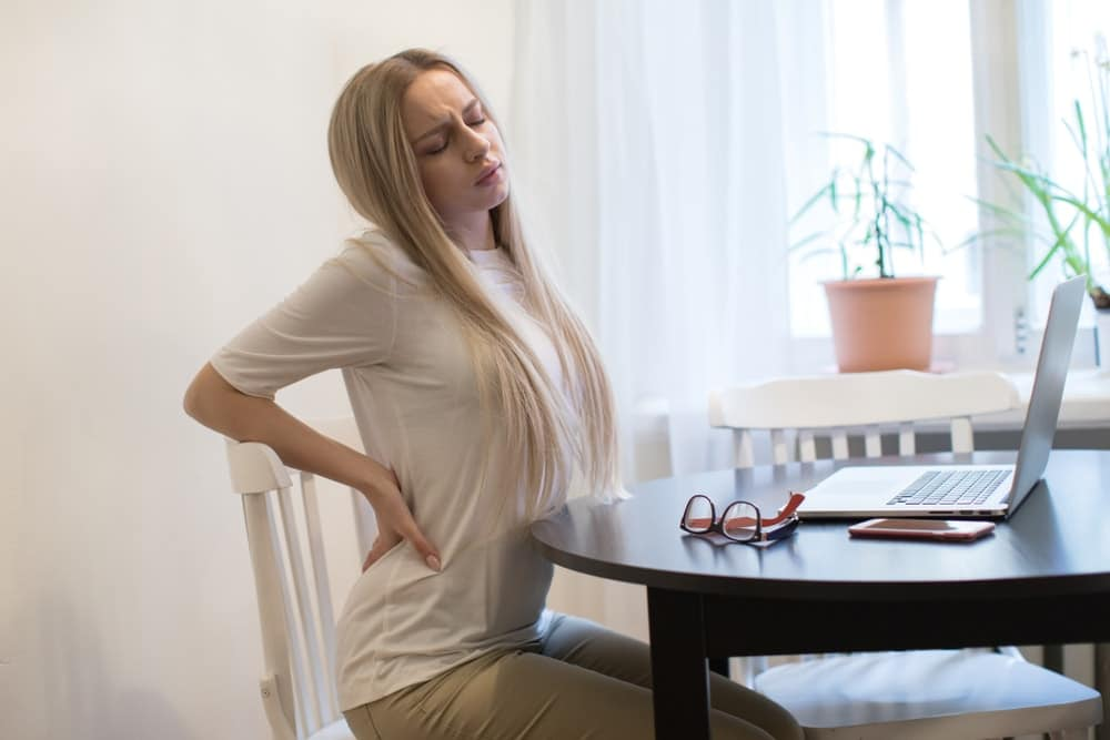 Woman sitting on a work desk having a back pain