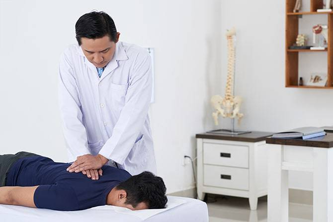 Doctor doing chiropractic work on a patient with back problems.