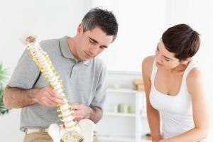 Male chiropractor shows female patient portion spine to explain sciatica pain