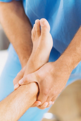 Chiropractor doing foot ankle adjustment for patient with foot pain