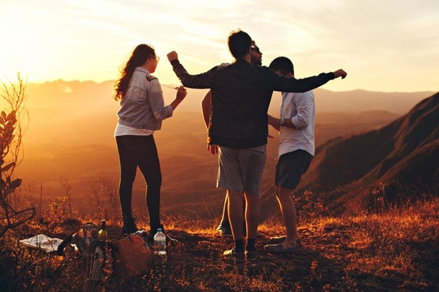 Four young people standing on top of a grassy mountain and having fun.
