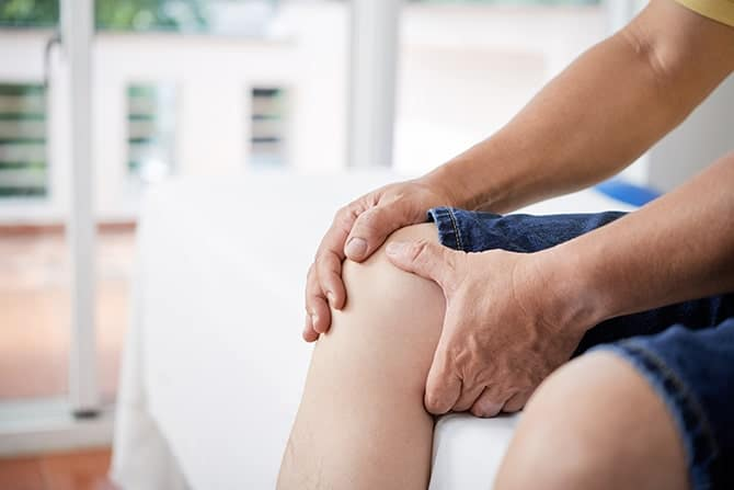 male holding his knee with both hands due to joint pain