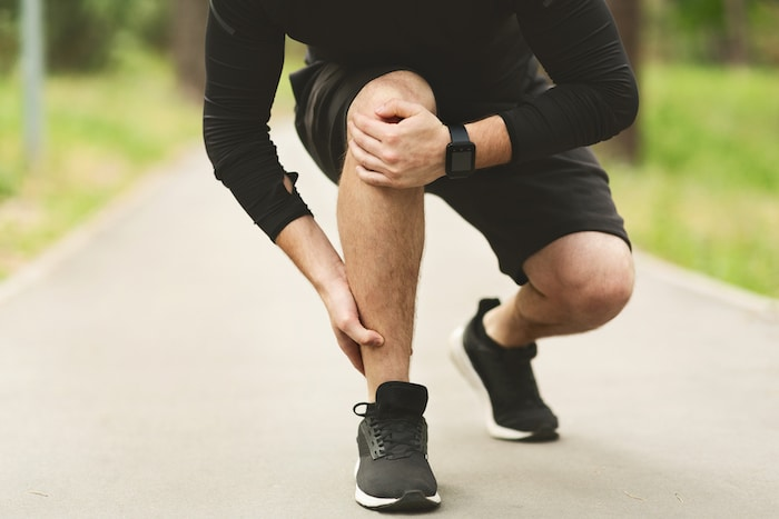 Male runner holding his ankle due to ankle pain