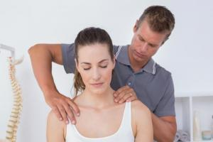 Chiropractor doing a treatment to female patient with neck pain.