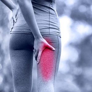 Woman holds numb leg because of sciatica