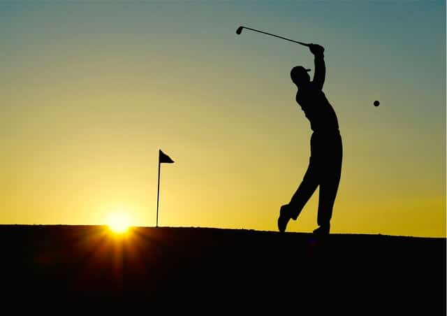 Silhouette of a man playing golf during sunset