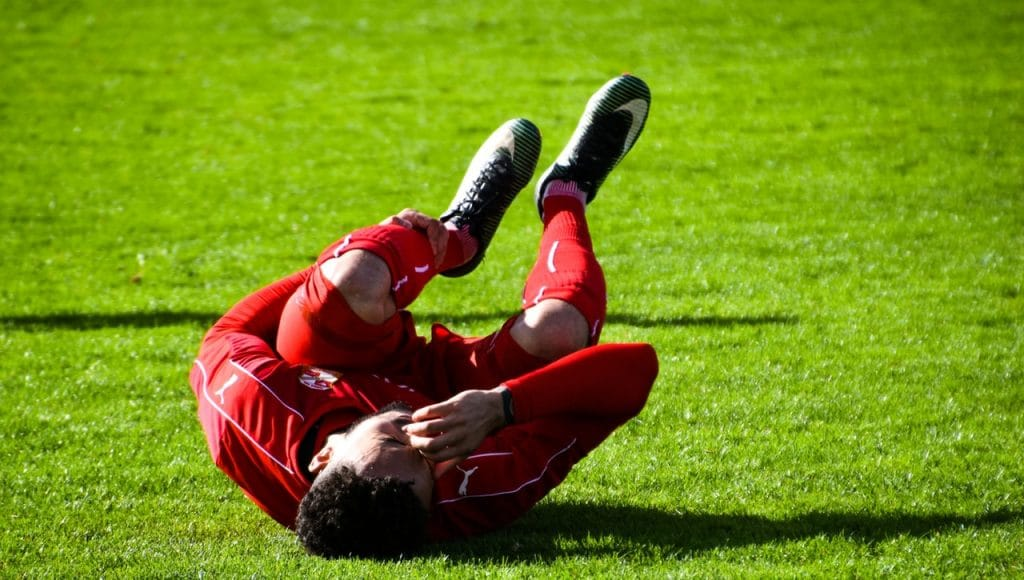 Soccer player crouching in pain due to sports injury. Treatment available at Hogan Spine & Rehab