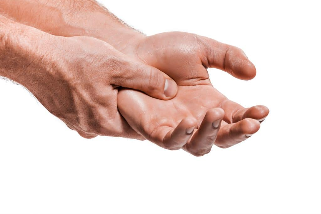 Shows man massaging his hand due to neuropathy