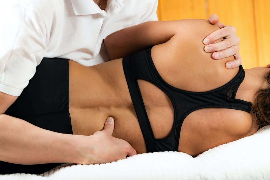 Chiropractor adjusting patients lower back