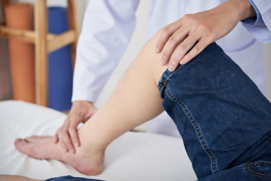 Doctor massaging the leg of a patient with neuropathy.