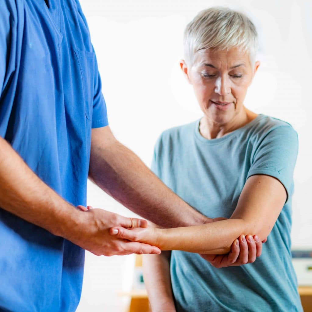 Chiropractor holding an elderly patient's arms while post surgery physical therapy.