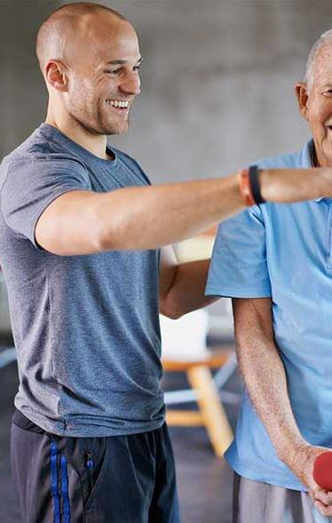 Physical therapist directing an elderly man for post surgery physical therapy.