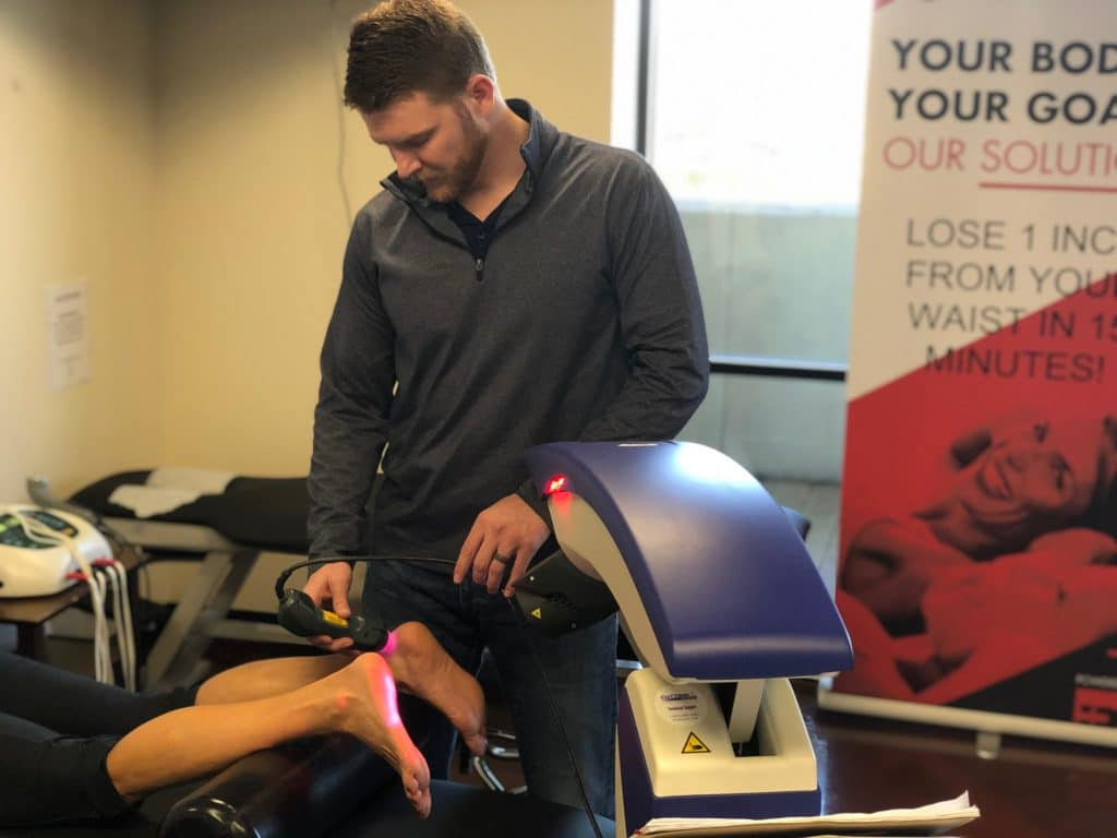 Hogan Chiropractic's doctor doing laser treatment on patient's neuropathic foot.