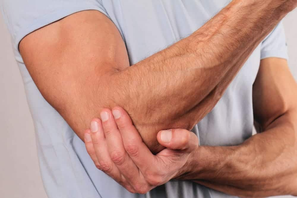Mascular man holding his elbow with pain
