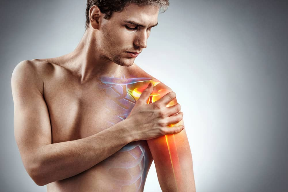 Man with shoulder pain holds left arm