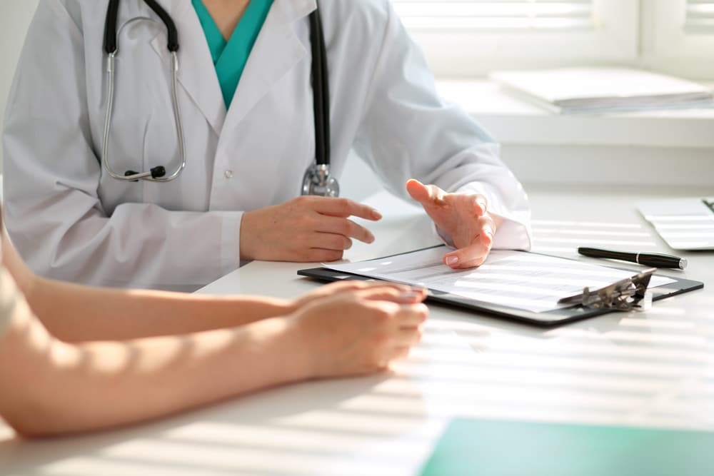 Pain management doctor sits with patient discussing findings