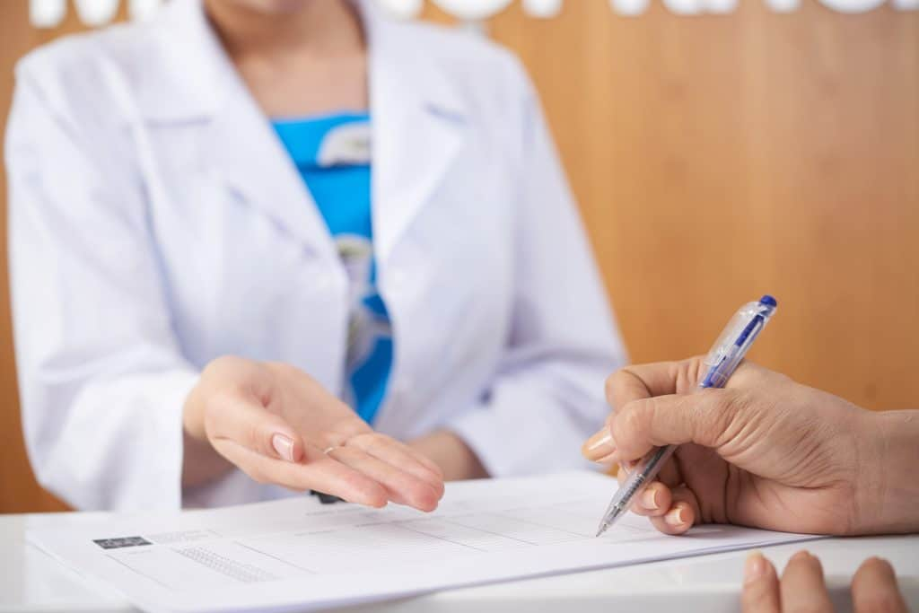 Female patient filling medical documents