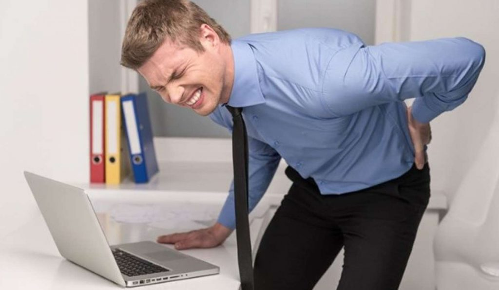 Office worker crouching in pain after standing up due to pinched nerve.