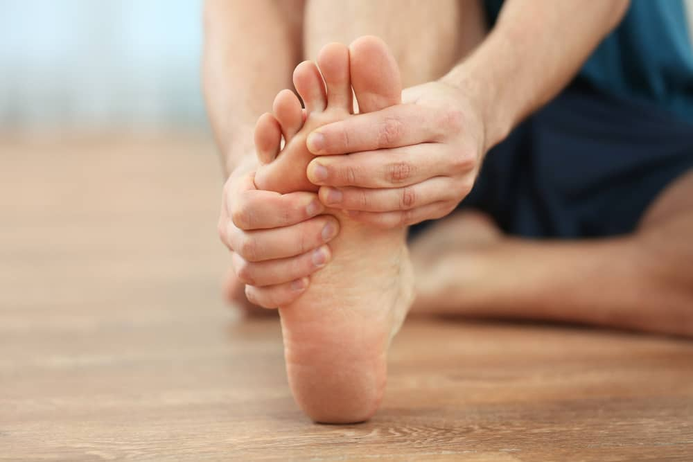 Man sitting on the floor holding his foot due to pain caused by plantar fasciitis.