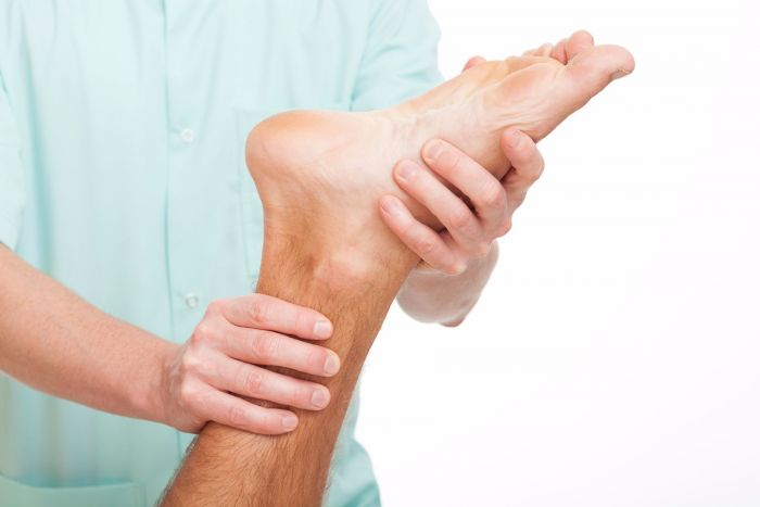 Chiropractor treating a patient's foot due to pain from plantar fasciitis.